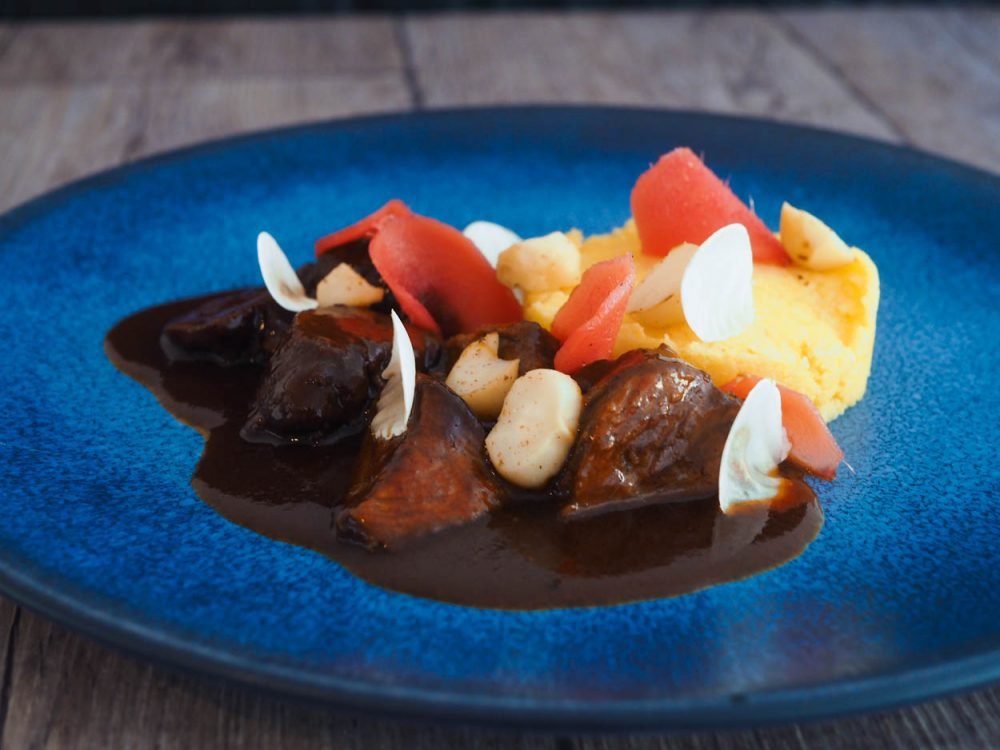 Braised pork cheeks, pink ginger, polenta and macadamia nuts