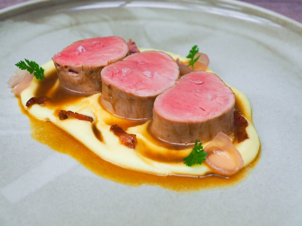 Pork tenderloin with potato purée, smoked bones sauce and pickled shallots