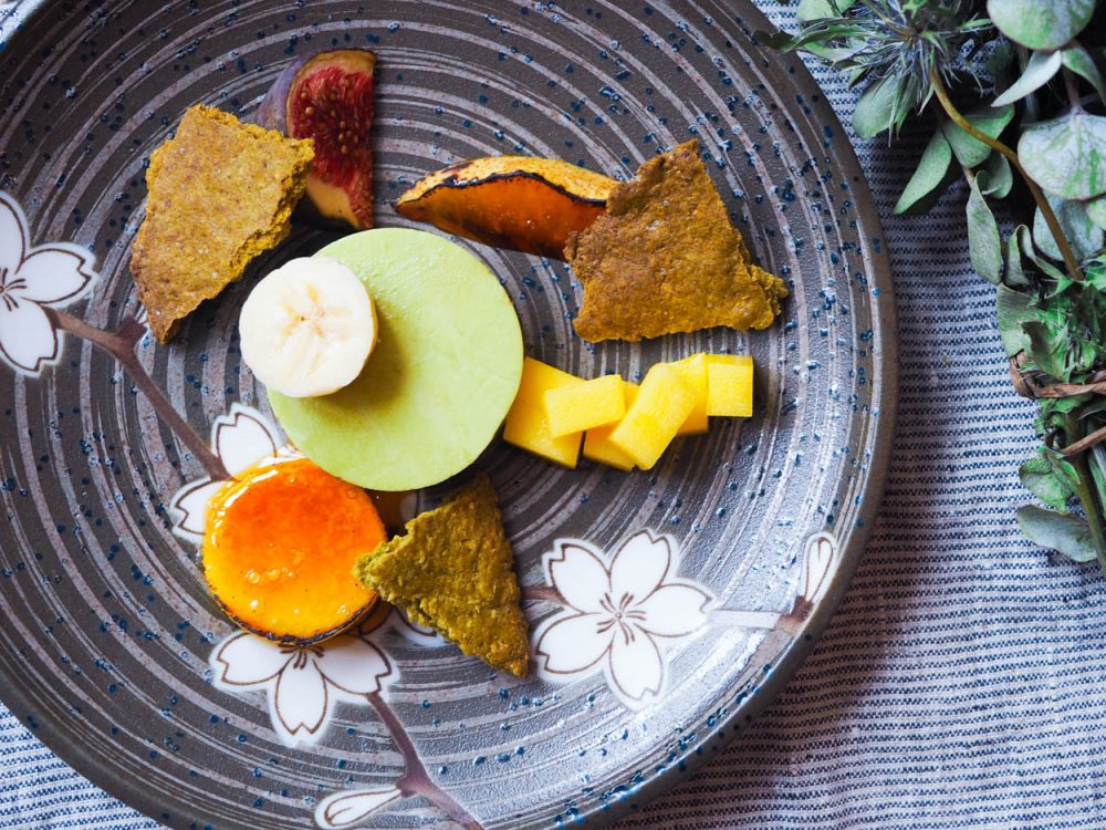 Matcha panna cotta with fruits and biscuits